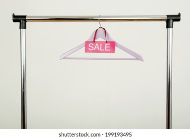 Empty hanger on a rack of clothes with the sale sign. Purple wood hanger, clearance concept.