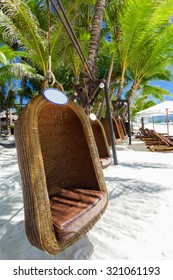 Empty hanging wicker chair on tropical beach, Philippines, Boracay