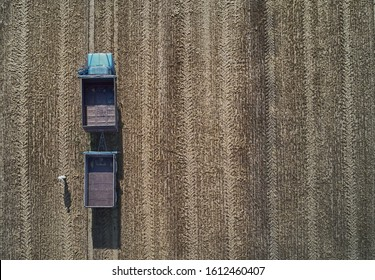 Empty harvester truck with trailer in field. Aerial view