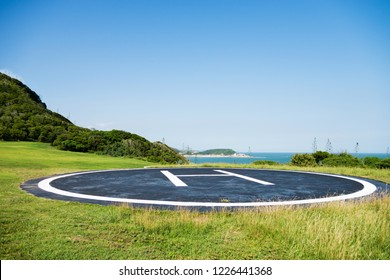 Empty helipad on island with blue sky background.