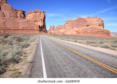 Empty highway in Arches National Park with sandstone rock formations in distance