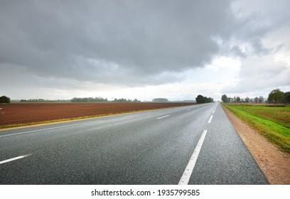 Empty highway (asphalt road) through the fields. Dramatic sky before the rain and thunderstorm. Concept landscape. Rural scene. Darkness, fall season, fickle weather, dangerous driving. Netherlands
