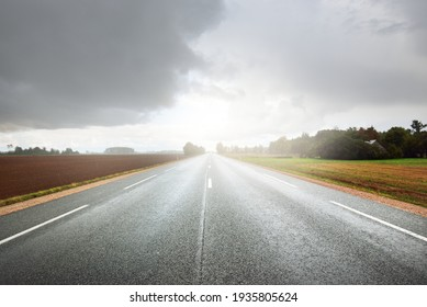 Empty highway (asphalt road) through the fields. Dramatic sky before the rain and thunderstorm. Concept landscape. Rural scene.