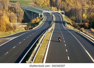 Empty highway leading across the bridge over the valley, in the foreground riding a motorcycle, electronic toll gates, deciduous forest in autumn colors, view from above