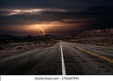 An empty highway leading to a lightning storm in the middle of the desolate desert near Moab, Utah, USA.