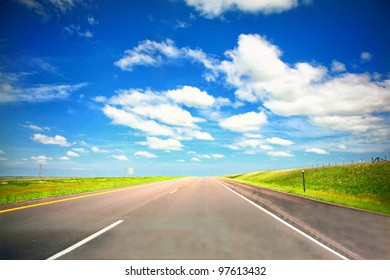 Empty Highway Open Road in Midwest with green grass and blue sky in summer
