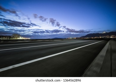 empty highway with skyline of vancouver at night.