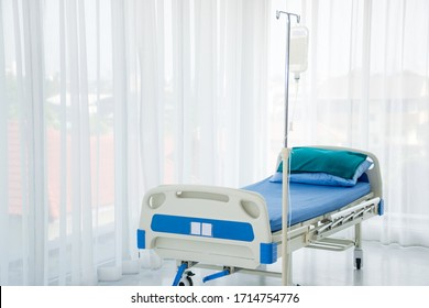 An empty hospital bed for sick patient with fluid bag and pole at a patient room or ward or an examination room at the hospital