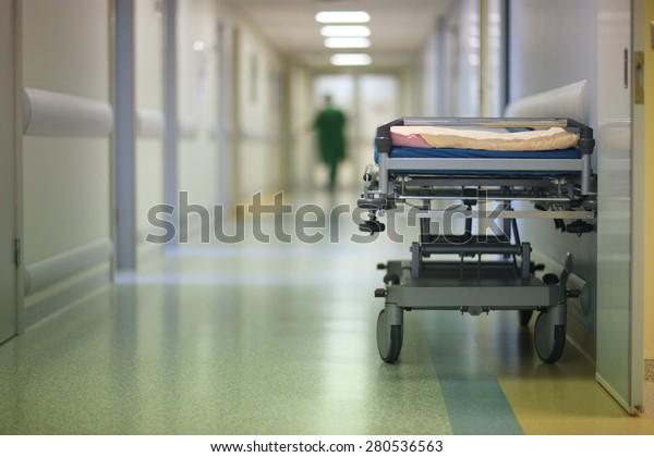 Empty hospital cot in a corridor