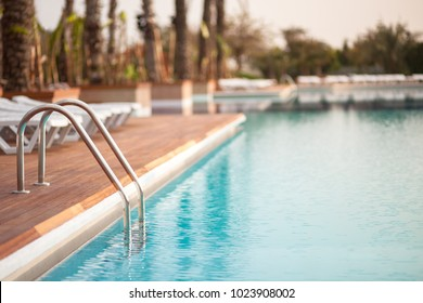 Empty hotel water pool with turquoise colour water at sunrise, focus on metal hand railing of staircase, copy space, place for text/ Relaxation, summer, vacation and water - concept/