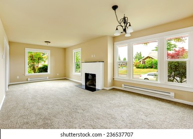Empty house interior. Family room with ivory walls and light grey carpet floor. Room has white brick background fireplace