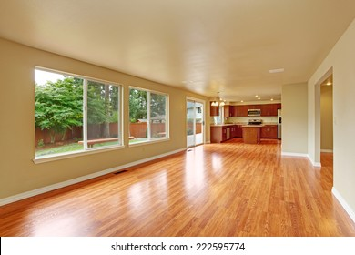 Empty house interior with new hardwood floor. Spacious empty living room with exit to backyard area and kitchen area