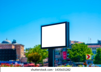 An empty huge poster mockup; white template placeholder of an advertising billboard on the rooftop of a modern building framed by trees; blank mock-up of an outdoor info banner