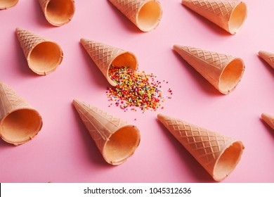 Empty ice-cream waffle cones and colorful sprinkles on pink background, side view