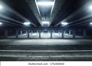 An empty illuminated motorway, bicycle road and pedestrian walkway under the bridge in a fog at night. Dark urban scene. Riga, Latvia. Dangerous driving, concept image