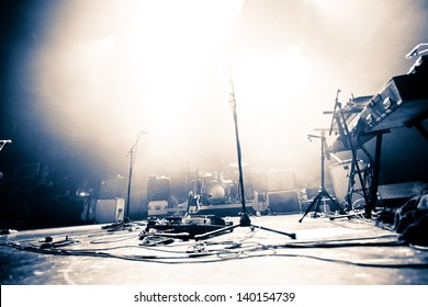 Empty illuminated stage with drumkit, guitar and microphones