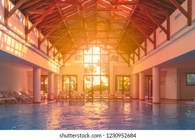 Empty Indoor pool at hotel. Nobody in water. Sunset sun shining in big window.