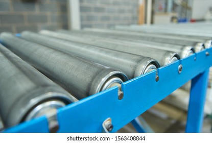 An empty industrial roller conveyor belt in a fully automated factory. roller conveyor to easily move heavy industrial goods around without the need for humans.future of industrial manufacture.