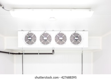 an empty industrial room refrigerator with four fans
