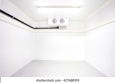 an empty industrial room refrigerator with two fans