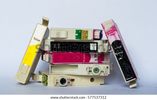 Empty ink cartridges with labels of various colors stacked on white background.