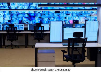 Empty interior of big modern security system control room, workstation with multiple displays, monitoring room with at security data center  Empty office, desk, and chairs at a main CCTV security data