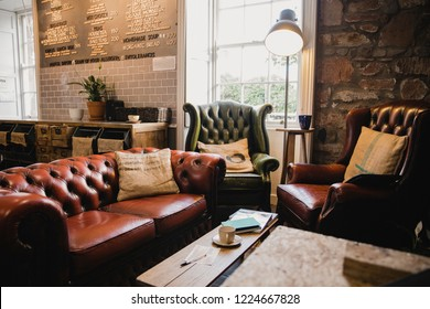 Empty interior of a small cafe, there is a seating area with leather sofas and a wooden table.