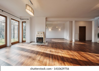 Empty interior of spacious living room interior with big windows retro fireplace and wooden floor