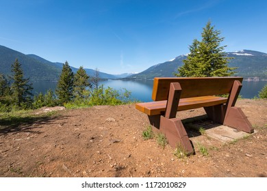 An empty and inviting wooden bench overlooking Kootenay Lake from Pilot Bay Provincial Marine Park on a sunny summer day