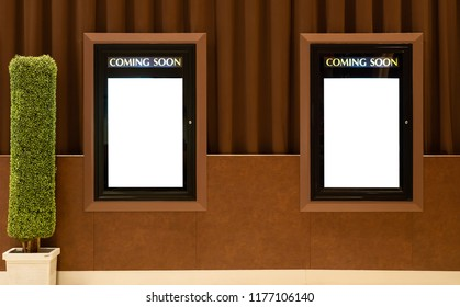 Empty isolated cinema poster panel on the wall of theater walkway, white blank mockup movie frame with coming soon text for insert design