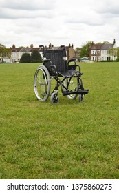 Empty isolated wheelchair on grass background in park with houses