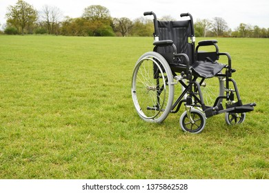 Empty isolated wheelchair on grass background in park