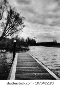 an empty jetty and a river in black and white this photo was taken with a pinhole film camera which corresponds to the camera characteristic