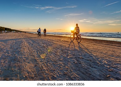 Empty Jurmala beach with lonely girl figure by bicycle, sun in a bicycle basket. Serenity concept. Scenic evening seascape
