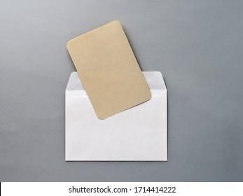 An empty Kraft brown card for an invitation or greeting and a white paper envelope on a gray textured background. Mock-up. Stylized stock photos. The view from the top.