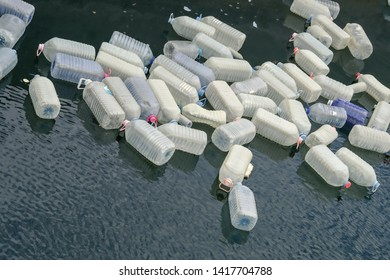 Empty large plastic containers, water cans floating in a bay in the Atlantic, waste, garbage disposal in the ocean, environmental pollution and plastic waste disposal on the oceans
