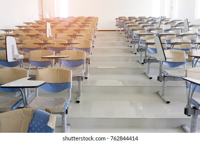 An empty lecture slope room / University classroom with blue chairs.