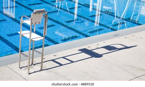Empty lifeguard chair next to bright blue pool