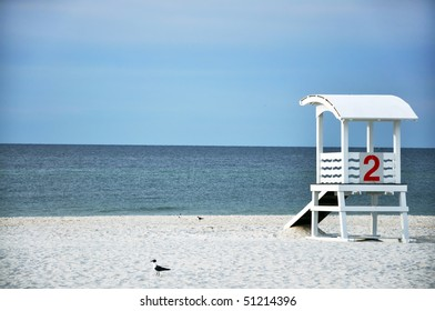 Empty lifeguard hut and seagulls on deserted beach.