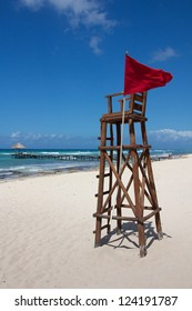 Empty lifeguard post with a red flag at a white, Caribbean beach under a clear sky.