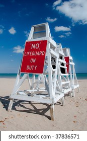 Empty lifeguard tower chair with not on duty sign