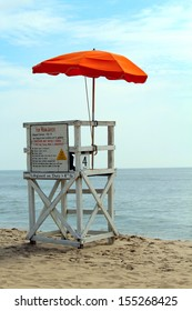 An empty lifeguard tower overlooking the ocean at the beach.