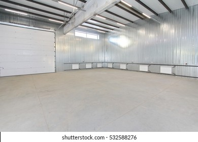 empty light parking garage, warehouse interior with large white gates and windows inside