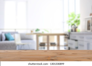 Empty light wooden table in modern kitchen. Mockup for design