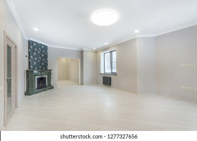 Empty living room interior with fireplace, laminate flooring and doorways