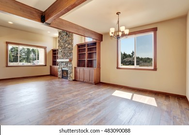 Empty living room interior with hardwood floor, stone fireplace and wooden shelves. Northwest, USA