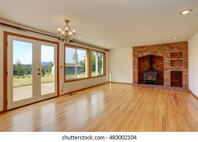 Empty living room interior in light tones with brick fireplace. Northwest, USA