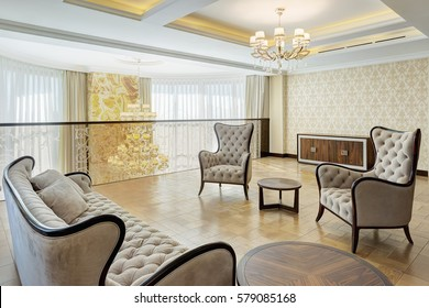 Empty living room on second floor with two armchairs, sofa and rounded wooden table between. Luxury crystal chandelier in center of ceiling.Interior of lighting room in beige and white colors.