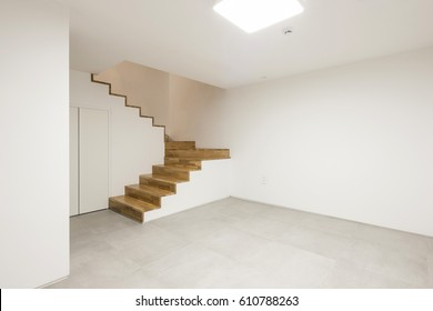 Empty living room with stair, window, lighting.