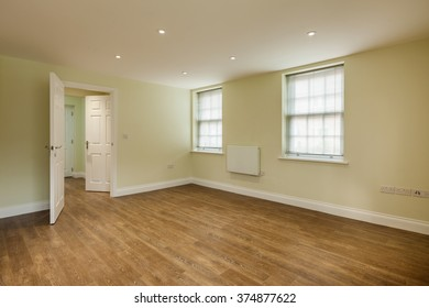 Empty living room within new apartment or house with twin windows and door opening to hall